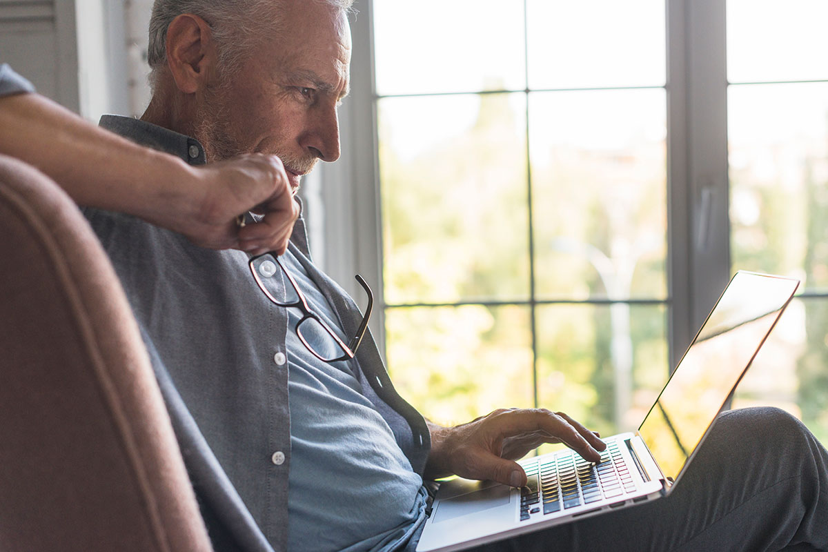Retired Man Looking at Computer | Naples Global Advisors, SEC Registered Investment Advisor