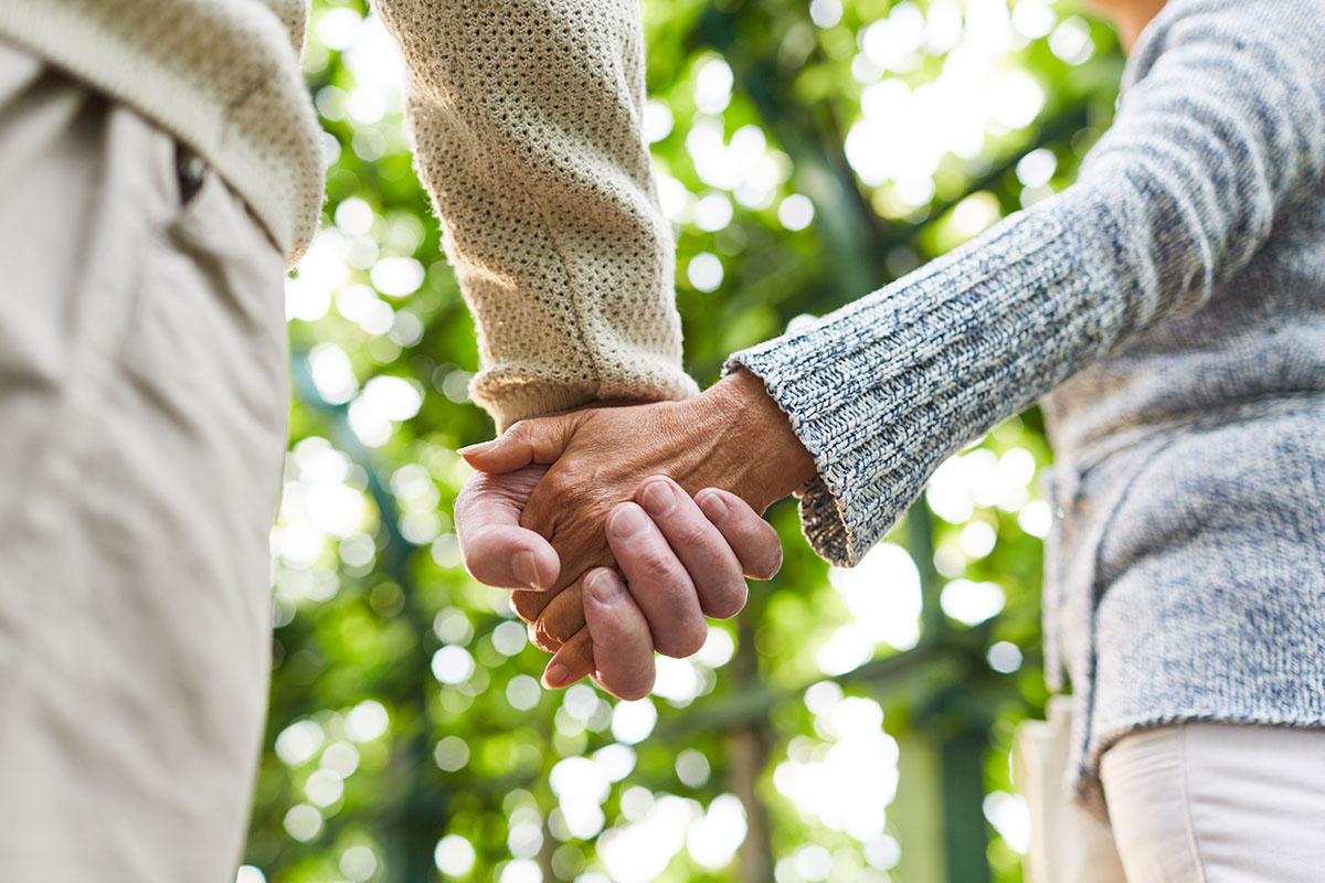 Retired Couple Holding Hands | Naples Global Advisors, SEC Registered Investment Advisor